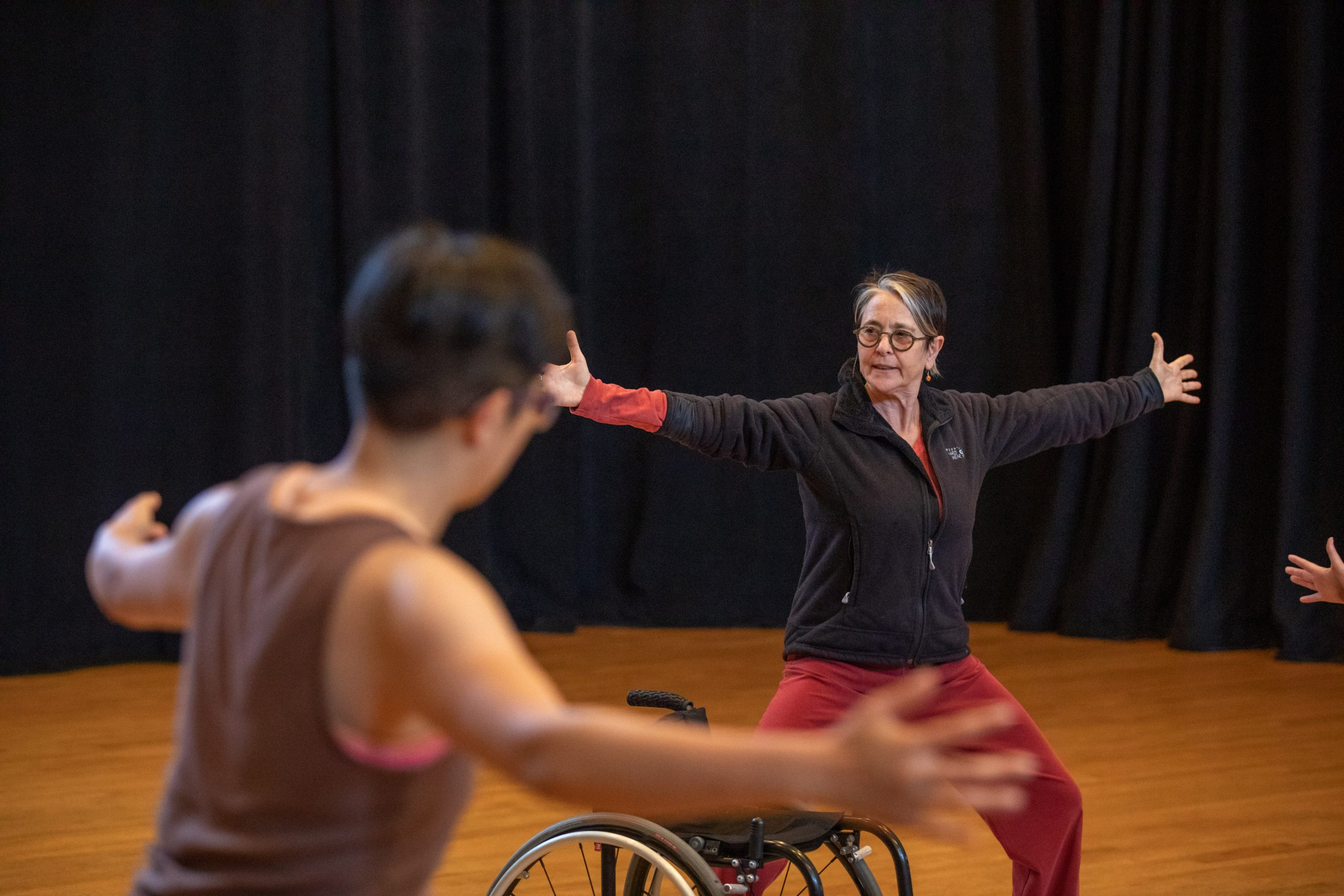 Victoria Marks demonstrates a movement during the 2019 Dancing Disability Workshop. Her arms are outstretched and knees slightly bent.