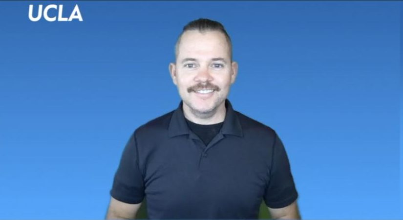 Benjamin Lewis, Lecturer in ASL at UCLA, stands in front of a blue background and smiles.